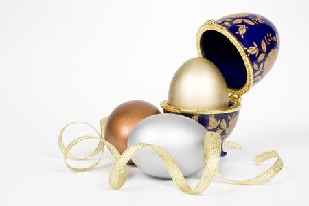 eggcup: Gold egg in a glass eggcup with gold tape, bronze and silver eggs. Isolated on a white background
