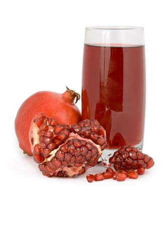 The cut pomegranate and garnet juice in a glass isolated on a white background. photo