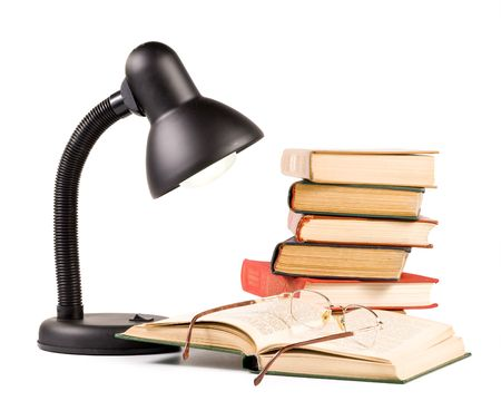 Stack of books, eyeglasses, and lamp isolated on a white background.  photo