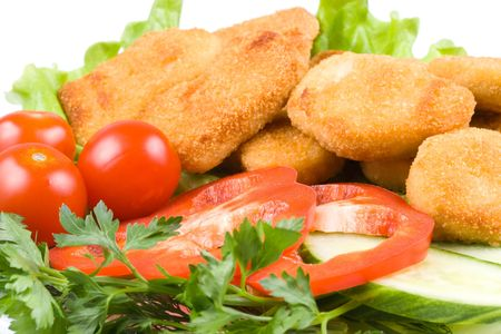 Appetizing fried chicken nuggets  with tomatoes, cucumber and pepper on salad leaves. Close-up. Selective focus. photo