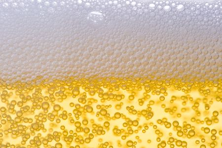 Background from fresh foamy beer with bubbles. Close-up.
