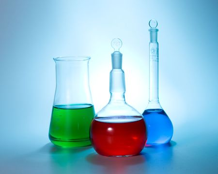 Various colorful flasks over blue tone background photo