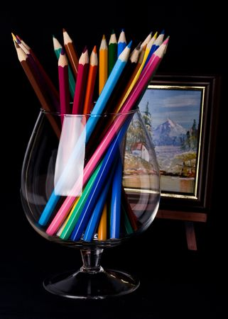 Colorful pencils in a glass on a black background photo
