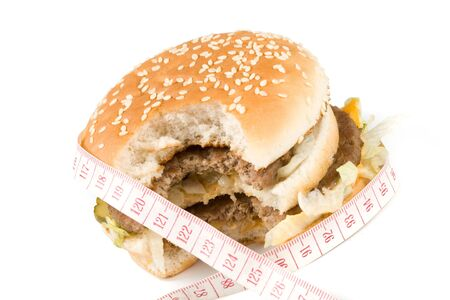 junkfood: Bread with fried meat, cheese, onion, lettuce and measuring tape isolated on a  white background.