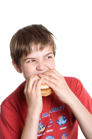 The boy eating a hamburger. Isolated on a white background. photo