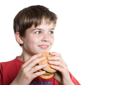 The boy eating a hamburger.  Selective focus on a hamburger. Isolated on a white background. Stock Photo - 3171555
