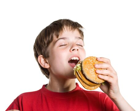 The boy eating a hamburger. Isolated on a white background. Stock Photo