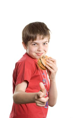 junkfood: The boy eating a hamburger. Isolated on a white background. Stock Photo