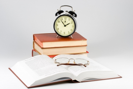 Old-fashioned black alarm clock, book and eyeglasses isolated on a white background photo
