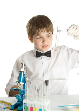 The boy with a microscope and various colorful flasks on a white background photo