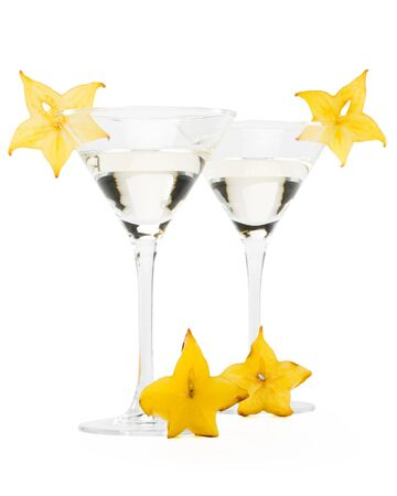 Glass of martini and slice of carambola on a white background photo