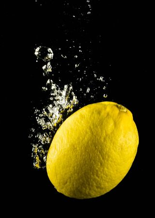 Fresh lemon in water on a black background with air vials photo