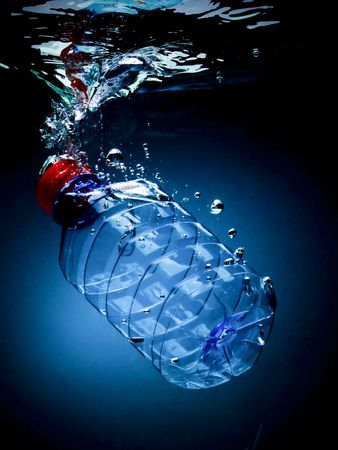 Bottled water on a blackblue background with air bubbles photo