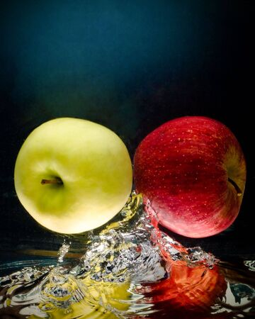 Fresh apple in water on a blackblue background with air bubbles photo