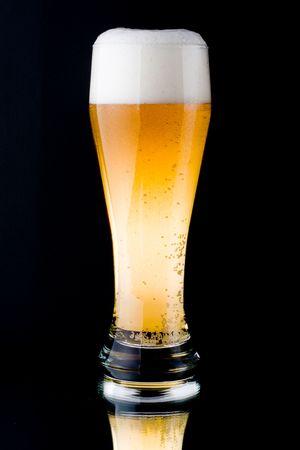 foamy: Fresh foamy beer in a glass on a black background.