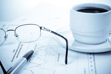 Pen, chart, cup of coffee and eyeglasses. Business still-life. photo