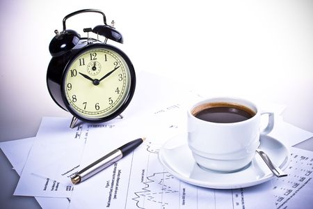 Pen, chart, alarm clock and cup of coffee. Business still-life. photo
