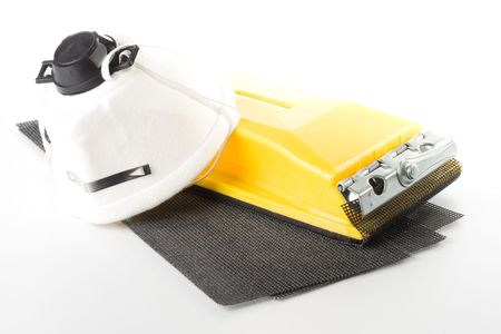 sanding block: Sandpaper with holder and dust mask on a white background