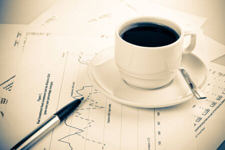 Pen, chart, and cup of coffee. Business still-life.