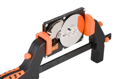 clamped: The  hard disk clamped in a manual clamp  on a white background. Concept for data compression. Stock Photo