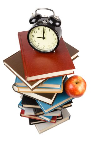 encyclopedias: Pile of books, alarm clock and apple isolated on a white background.  Concept for Back to school Stock Photo