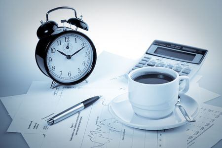 Pen, chart, calculator, alarm clock and cup of coffee. Business still-life. photo