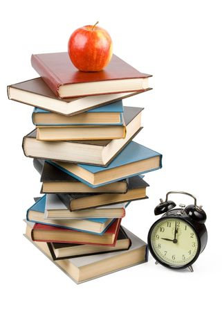 Pile of books, alarm clock and apple isolated on a white background.  Concept for Back to school photo