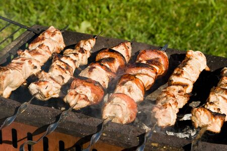 Shish kebab preparation on a brazier. Outdoor picnic. Close up. photo