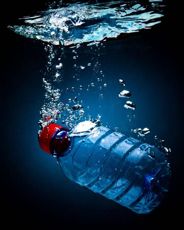 Bottled water on a blackblue background with air bubbles