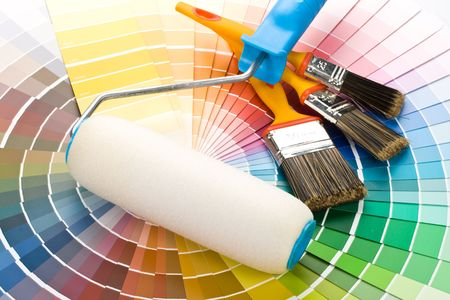 redecorating: Brushes and paint-roller on a colour guide