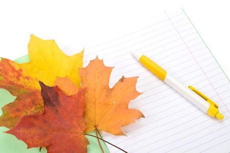 Writing-book, pen and autumn leaves on a white background. Concept for  photo