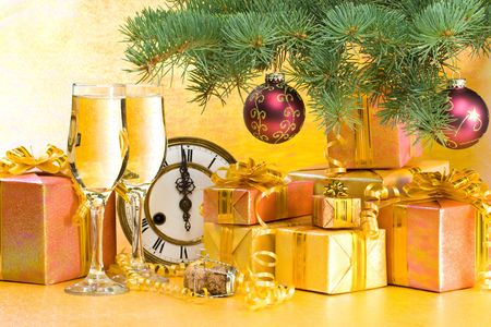 Decoration with an antique clock, firtree branch, gift boxes and champagne glasses photo