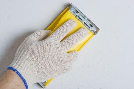 Appartement de réparation. Traitement d'un mur par un papier de verre.