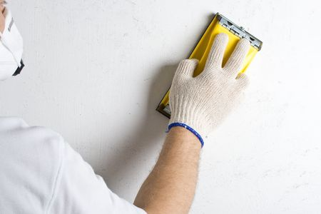 sanding block: Apartment repair. Processing of a wall by an sandpaper.