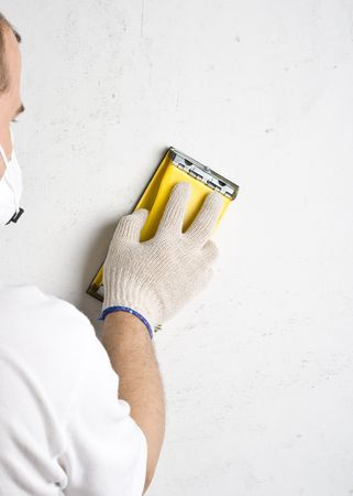 Apartment repair. Processing of a wall by an sandpaper. Stock Photo - 3915884