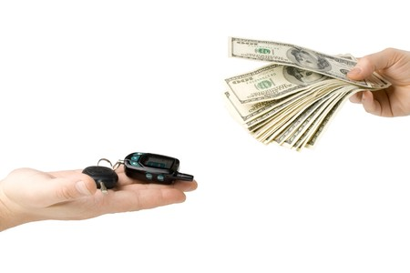 Hand with money and car keys on a white background photo