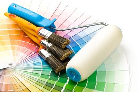 pintor: Pinceles y rodillos de pintura-en una gu�a de color Foto de archivo