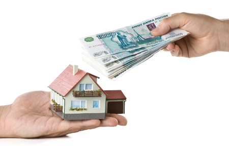roubles: Hands with money and miniature house on a white background Stock Photo