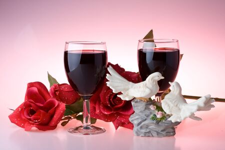 Two glasses of wine, rose and figurine on a pink background Stock Photo - 4096433