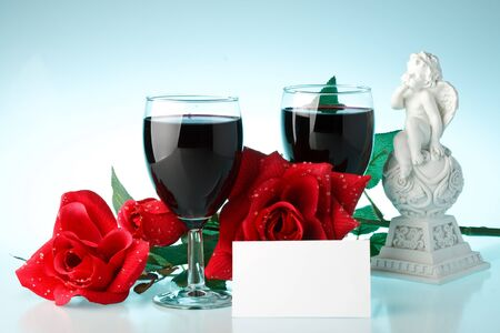 Two glasses of wine, rose and the cupid on a blue background photo