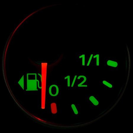 A gas gauge shows petrol level on a black background photo