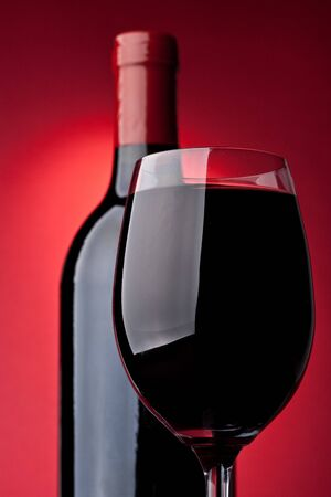 Bottle of a red vintage wine and glass on a red background Stock Photo - 4142151