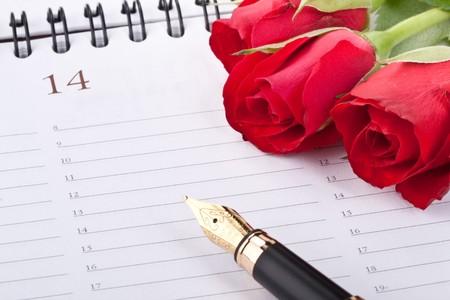 calendario escolar: Rosas rojas, pluma y la p�gina de calendario. D�a de San Valent�n tarjeta.