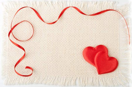 Two hearts and red tape on a canvas. Valentines day card. photo