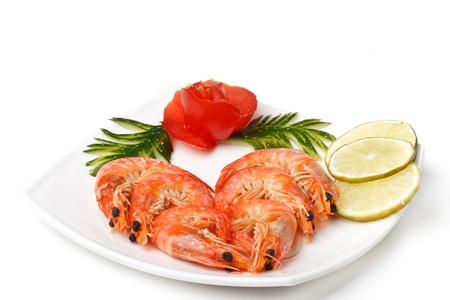 The boiled tiger shrimps served with vegetables on a white background photo