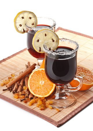 Two glasses of mulled wine, orange and spices on a white background photo