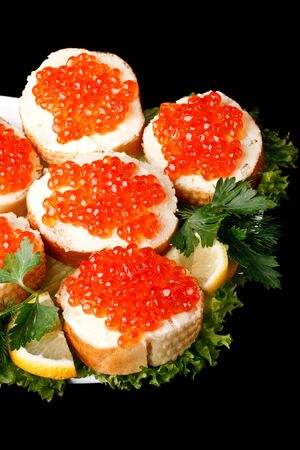 Sandwiches with red caviar and greens on a black background photo