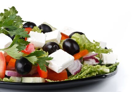 Appetizing greek salad on a plate. Close up. Stock Photo