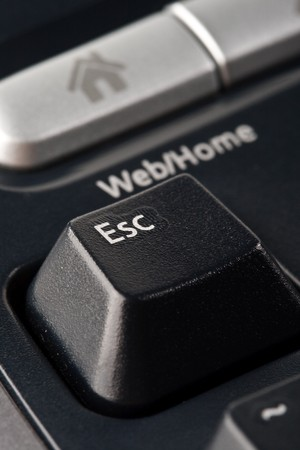 esc: Modern black ergonomic computer keyboard. Close up. Focus on ESC button.