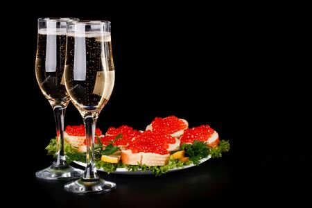 Sandwiches with red caviar and two glasses of champagne on a black background photo